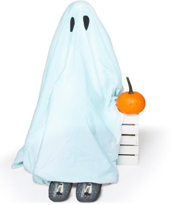 child dressed as a cute ghost sitting with a pumpkin