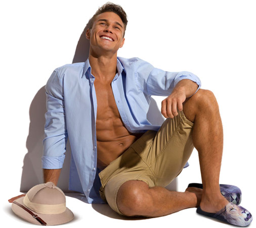 Handsome young man in unbuttoned blue shirt and beige shorts sitting barefoot against sunny wall, smiling and looking away. Full length studio shot isolated on white.